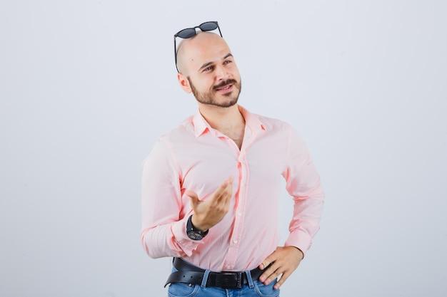 Jonge man die hand opsteekt terwijl hij iets bespreekt in een roze shirt, spijkerbroek, zonnebril vooraanzicht.