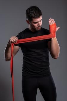 Jonge man die handen inpakt met rode bokshandentape