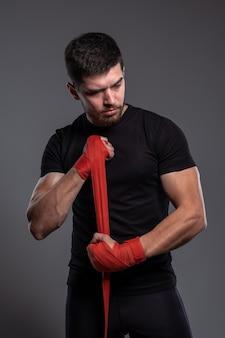 Jonge man die handen omwikkelt met rode bokstape