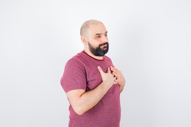 Jonge man die handen op de borst rust in een roze t-shirt en er optimistisch uitziet, vooraanzicht.