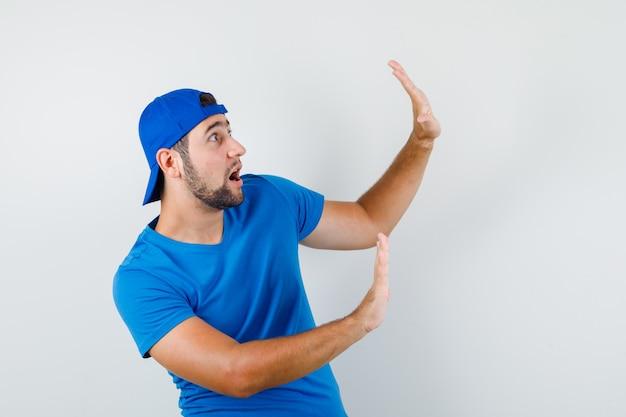 Jonge man die handen op preventieve wijze in blauw t-shirt en pet opheft en bang kijkt