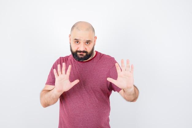 Jonge man die handen opsteekt om te verdedigen in het vooraanzicht van het roze t-shirt.