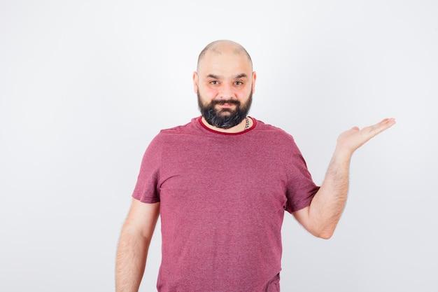 Jonge man die handen uitrekt alsof hij iets in een roze t-shirt vasthoudt en er optimistisch uitziet, vooraanzicht.