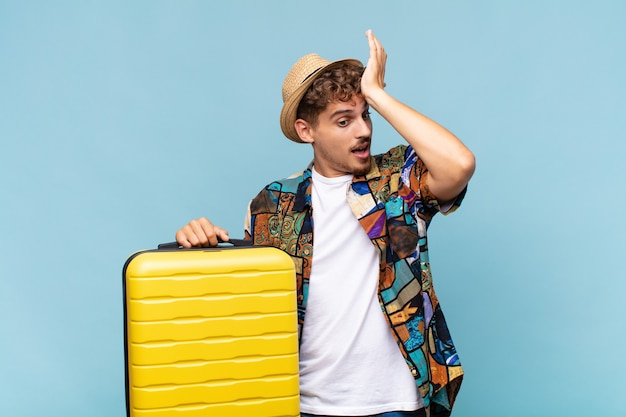 Jonge man die handpalm naar voorhoofd opheft, denkend oeps, na het maken van een domme fout of het herinneren, zich dom voelen. vakantie concept