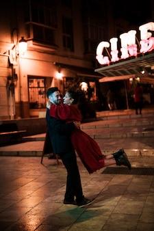 Jonge man die hangende lachende vrouw op straat in avond omhelzen