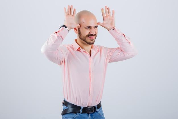 Jonge man die het gebaar van de stierenhoorn toont terwijl hij zijn tong uitsteekt in een roze shirt, spijkerbroek en er grappig uitziet, vooraanzicht.