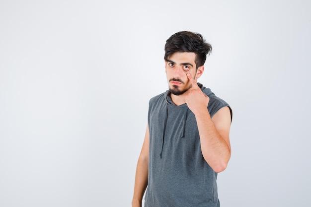 Jonge man die het gebied rond de ogen met wijsvinger in grijs t-shirt uitrekt en er serieus uitziet