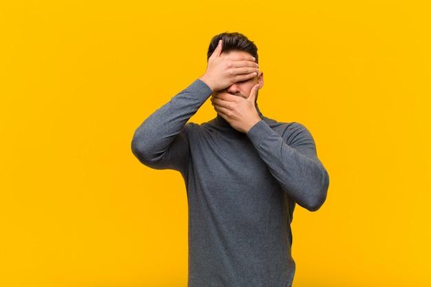 Jonge man die het gezicht bedekt met beide handen en nee zegt tegen de camera! afbeeldingen weigeren of foto's verbieden over een oranje muur