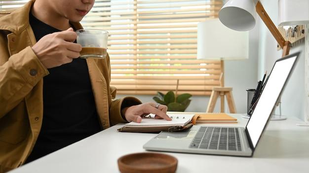 Jonge man die hete koffie drinkt en laptopcomputer gebruikt.