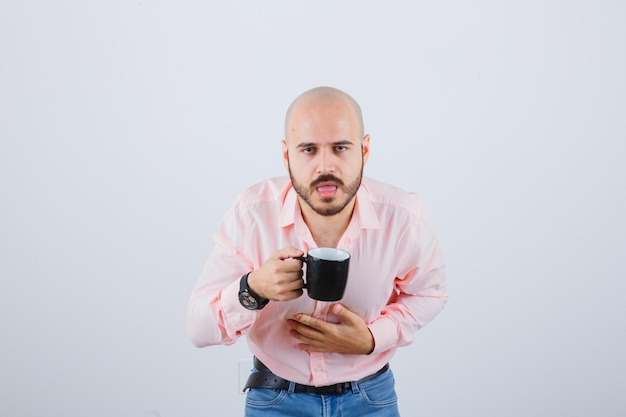 Jonge man die hete thee drinkt terwijl hij zich slecht voelt in een roze shirt, spijkerbroek en er pijnlijk uitziet. vooraanzicht.