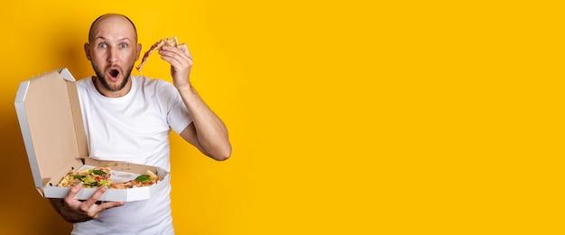 Jonge man die hete verse pizza eet met verpakking op een gele ondergrond. banier.