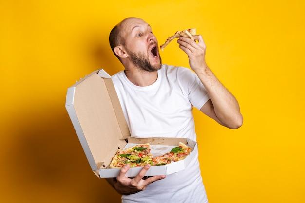 Jonge man die hete verse pizza eet met verpakking op een gele ondergrond.
