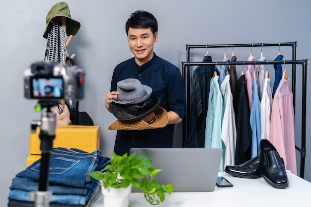 Jonge man die hoed en kleding online verkoopt door livestreaming van de camera. zakelijke online e-commerce thuis