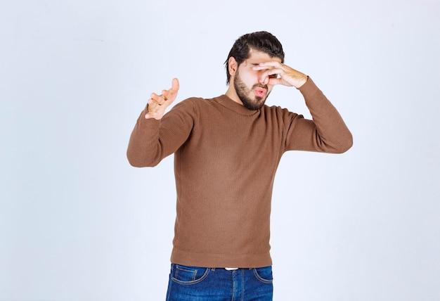 Jonge man die iemand afwijst die een gebaar van walging toont.