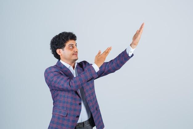 Jonge man die iets laat zien of verwelkomt in shirt, jas en er knap uitziet. vooraanzicht. Gratis Foto