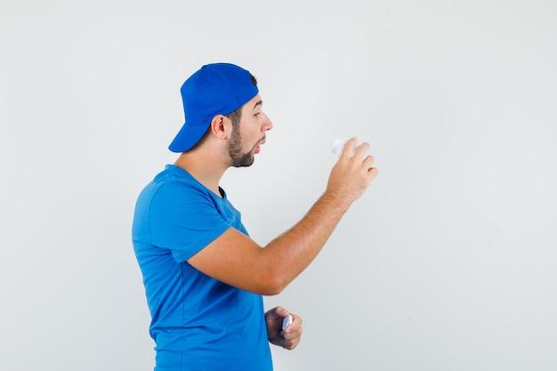 Jonge man die in blauw t-shirt en glb fles van pillen onderzoekt en nieuwsgierig kijkt.
