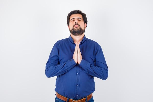 Jonge man die in koningsblauw overhemd wenst en er hoopvol uitziet, vooraanzicht.