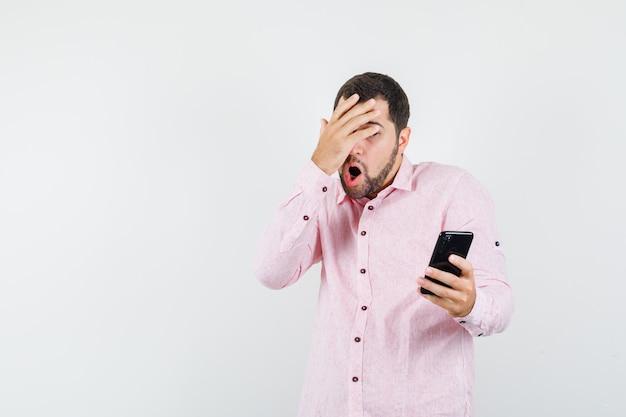 Jonge man die in roze overhemd mobiele telefoon met hand op ogen houdt en bang kijkt