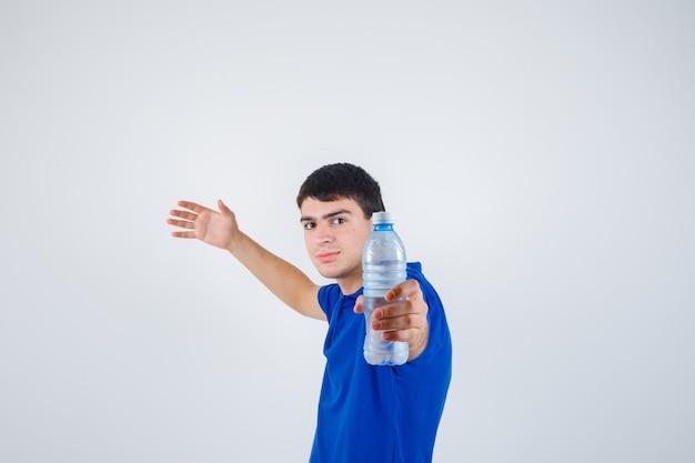 Jonge man die in t-shirt plastic fles houdt, de andere hand opheft en zelfverzekerd kijkt, vooraanzicht.