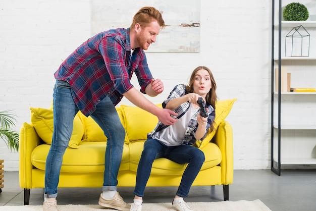 Jonge man die joystick van de hand van zijn meisje thuis probeert te nemen
