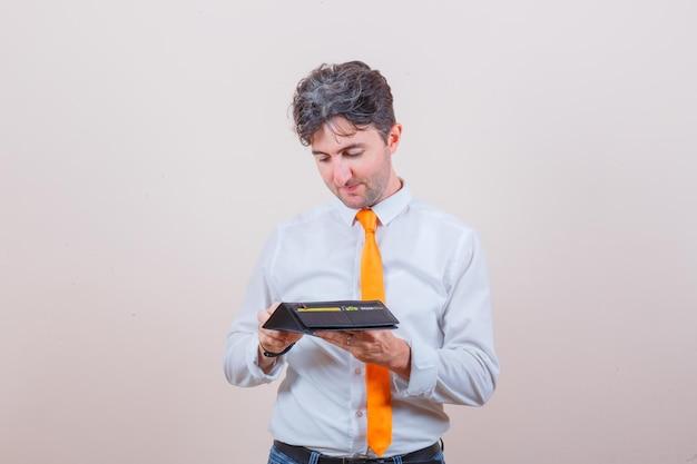 Jonge man die kaart uit portemonnee haalt in overhemd, stropdas, spijkerbroek