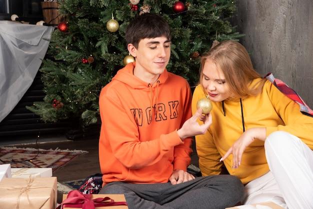 Jonge man die kerstbal toont aan zijn vriendin op kerstinterieur.