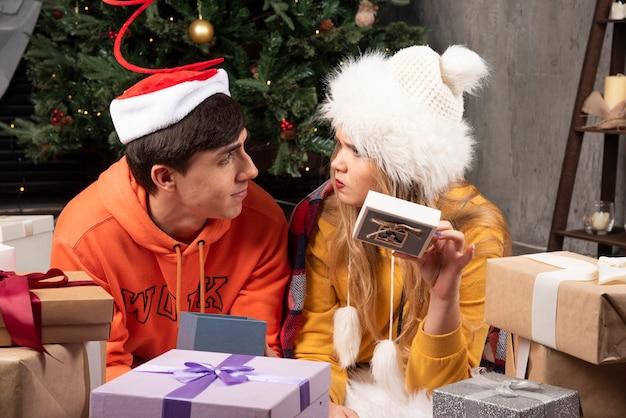 Jonge man die kerstcadeau geeft aan zijn boze vriendin.