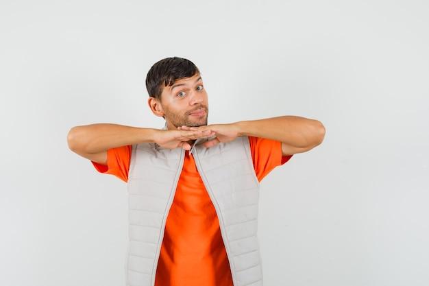 Jonge man die kin op geklemd vingers in t-shirt, jasje steunt en er schattig uitziet.
