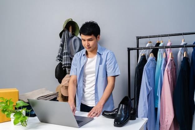 Jonge man die kleding en accessoires online verkoopt via live streaming van laptopcomputer. zakelijke online e-commerce thuis