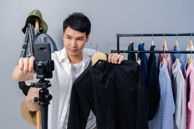 Jonge man die kleding en accessoires online verkoopt via live streaming van smartphone. zakelijke online e-commerce thuis
