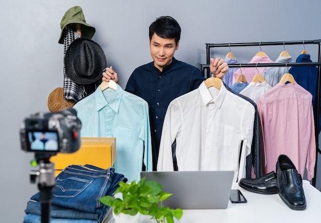 Jonge man die kleding en accessoires online verkoopt via livestreaming van de camera. zakelijke online e-commerce thuis