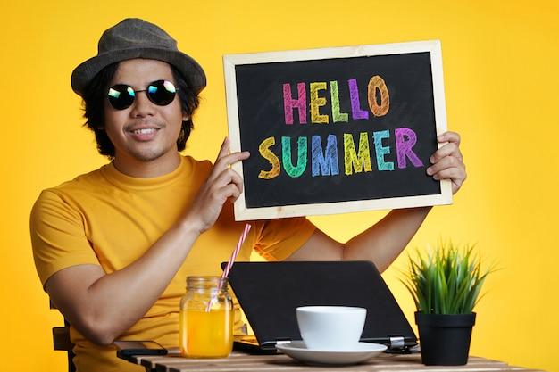 Jonge man die kleurrijke hello-de zomertekst op bord houdt terwijl het werken