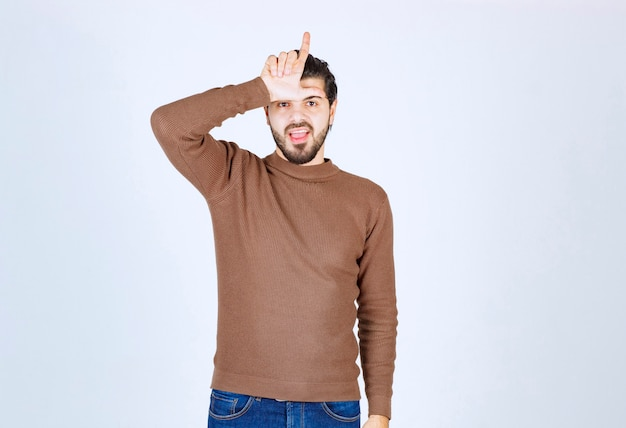 Jonge man die l-vingerteken maakt over voorhoofd dat op witte muur wordt geïsoleerd. hoge kwaliteit foto