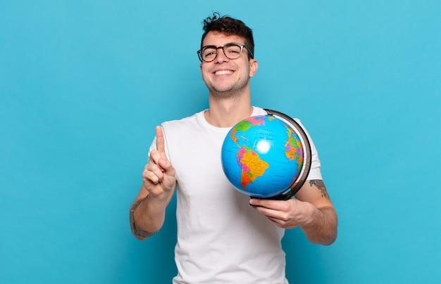Jonge man die lacht en er vriendelijk uitziet, nummer één toont of eerst met de hand