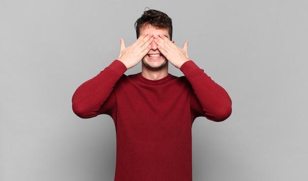 Jonge man die lacht en zich gelukkig voelt, zijn ogen met beide handen bedekt en wacht op een ongelooflijke verrassing