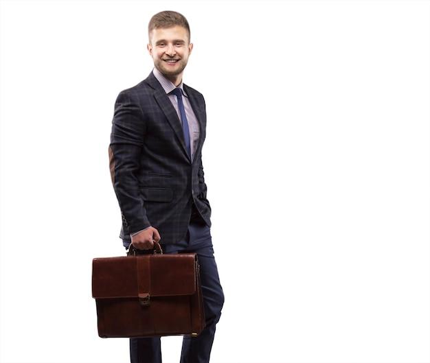Jonge man die lacht in een pak met een aktetas in zijn handen