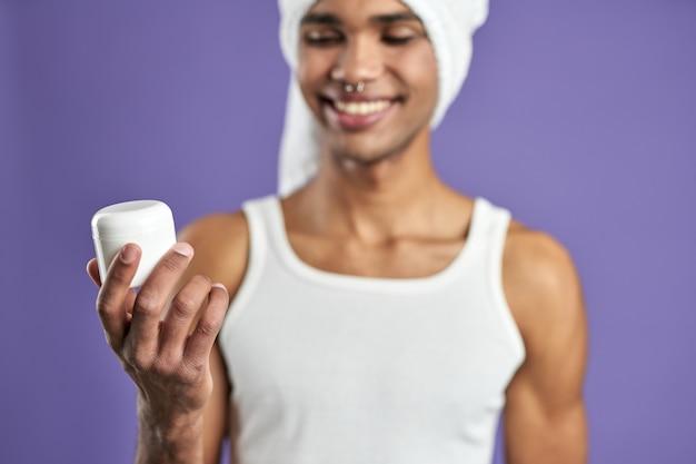 Jonge man die lacht met cosmetische gezichtscrème in de hand op paarse achtergrond close-up portret