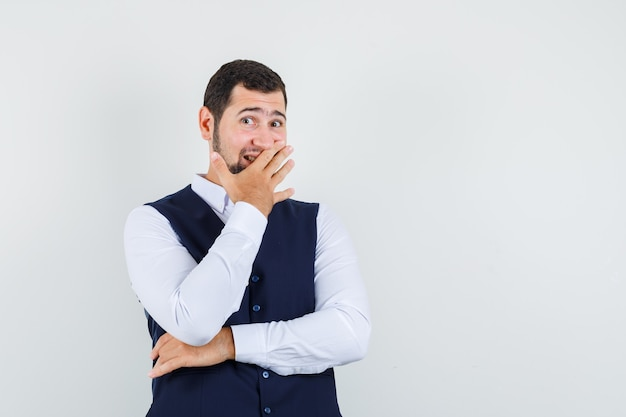 Jonge man die lacht met hand op mond in shirt en vest vooraanzicht.