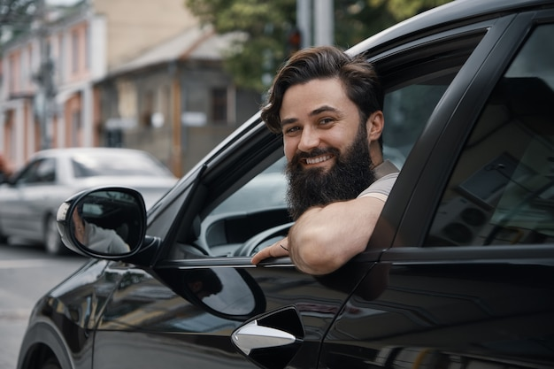 Jonge man die lacht tijdens het besturen van een auto