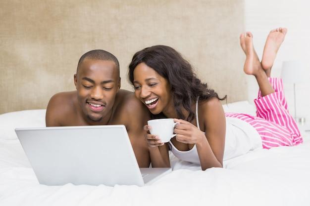 Jonge man die laptop en vrouwen de kop van de holdingskoffie gebruiken