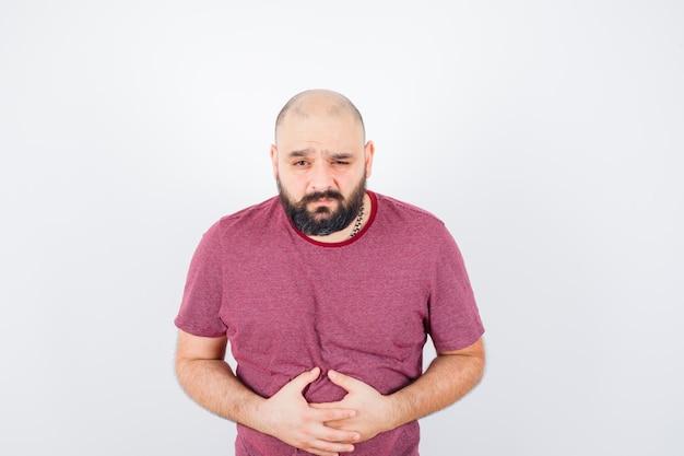 Jonge man die last heeft van buikpijn in roze t-shirt en er pijnlijk uitziet. vooraanzicht.