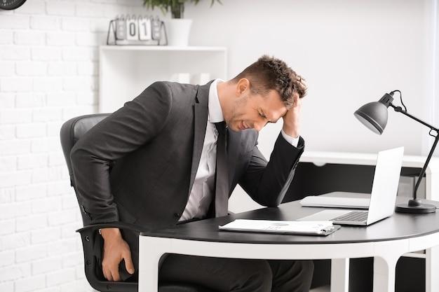Jonge man die lijdt aan aambeien in kantoor