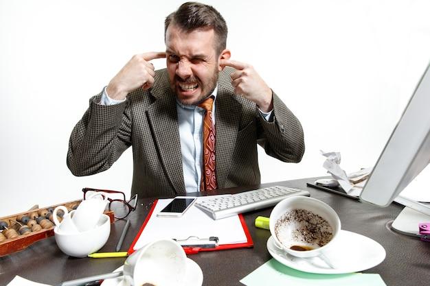 Jonge man die lijdt aan de gesprekken van de collega's op kantoor