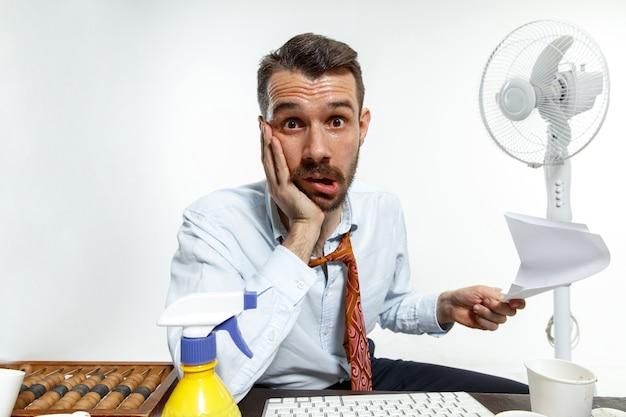 Jonge man die lijdt aan de hitte op kantoor