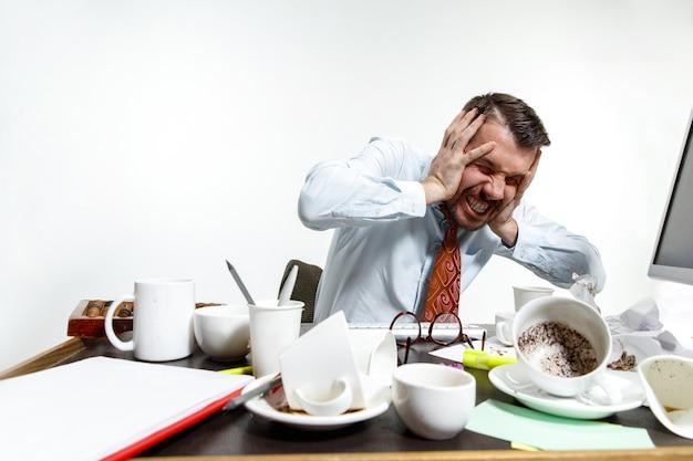 Jonge man die lijdt aan het lawaai op kantoor
