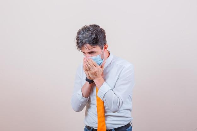 Jonge man die lijdt aan hoest in overhemd, stropdas, masker, spijkerbroek en er ziek uitziet