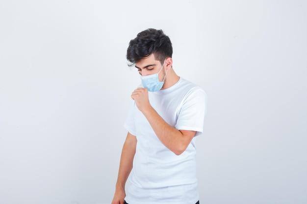Jonge man die lijdt aan hoest in wit t-shirt, masker en er ziek uitziet