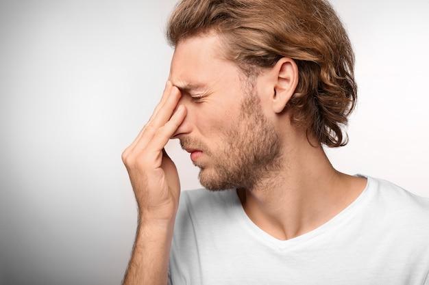 Jonge man die lijdt aan hoofdpijn op lichte ondergrond