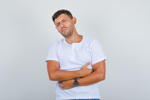 Jonge man die lijdt aan maagpijn in wit t-shirt en ziek, vooraanzicht kijkt