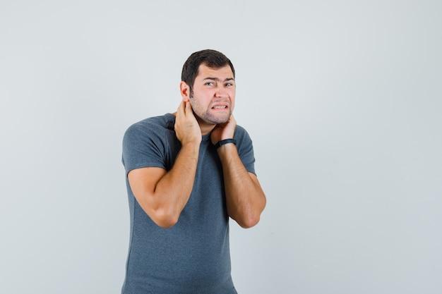 Jonge man die lijdt aan nekpijn in grijs t-shirt en onwel kijkt